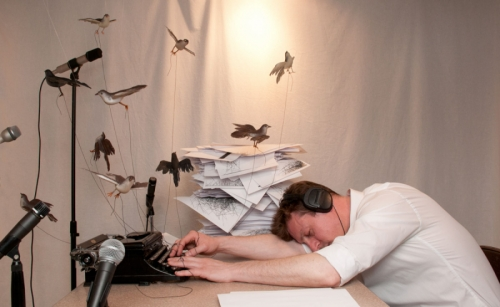figure with birds tied to each of his fingers, collapsed at desk in front of his typewriter as microphones capture the birds' songs and pipe them into the figures ears via headphones (large view)