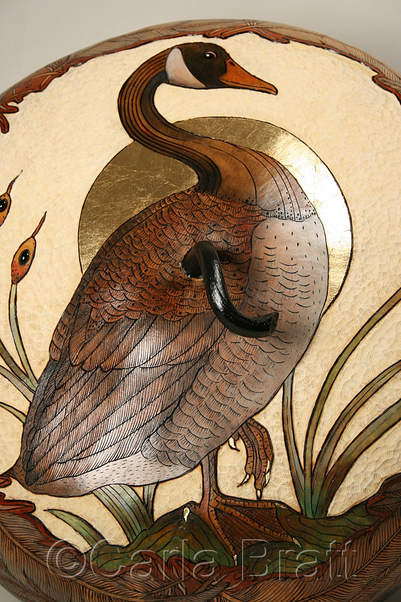 Fine art gourd of Canada goose image, centered with cattail details. Lightly carved ivory background with wood burned feather border. It has a gold leaf  moon.  Hand painted in browns, greens, greys, & ivories By gourd artist & printmaker, Carla Bratt. (large view)